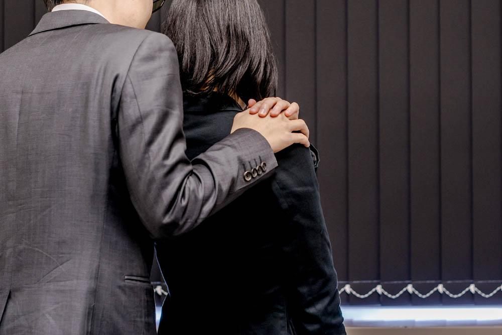 女性の肩に手を回す不倫中の男女